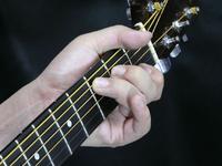 指が寝ていて隣の弦に触れています